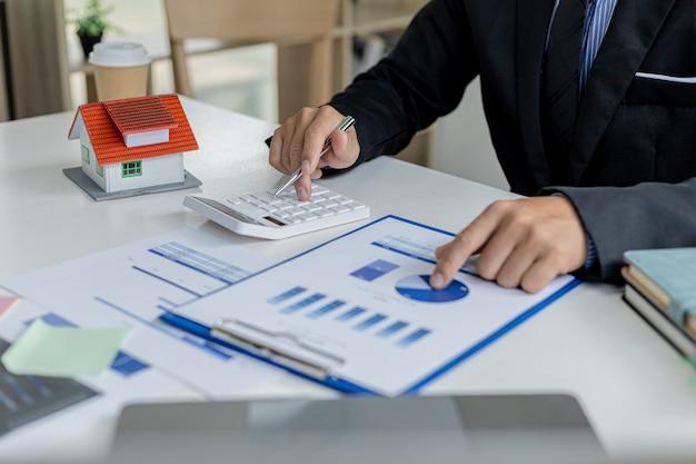 L'homme d'affaires appuie sur une calculatrice pour calculer le montant sur un document de vente de lotissement, il rencontre le directeur des ventes pour placer une vente et faire des promotions, des plans marketing pour augmenter les ventes