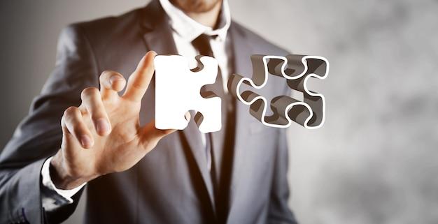 Homme d'affaires appuie sur le puzzle à l'écran