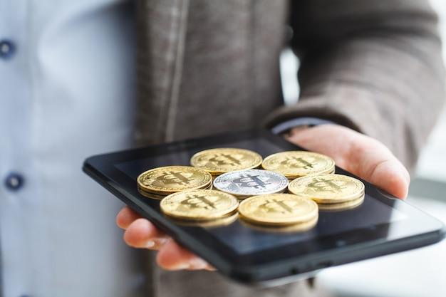 Homme d'affaires en appuyant sur le bouton bitcoin sur tablette