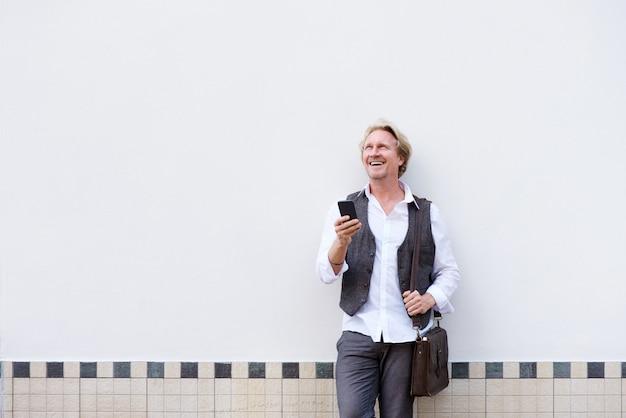 Homme affaires, appuyé, mur, téléphone portable