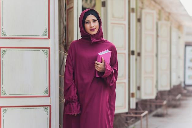 Homme d'affaires arabe confiant souriant et promenades de dubaï affaires arabes vumen hijab est dans les rues contre les gratte-ciel de dubaï la femme est vêtue d'une abaya noire