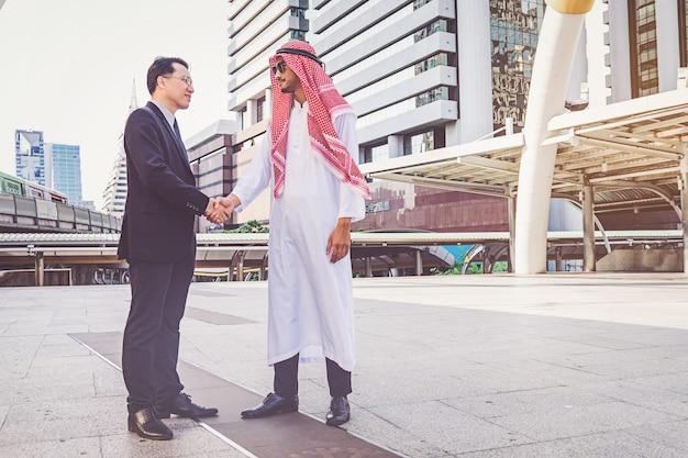 Homme d'affaires arabe donnant une poignée de main à son partenaire, sur un chantier de construction