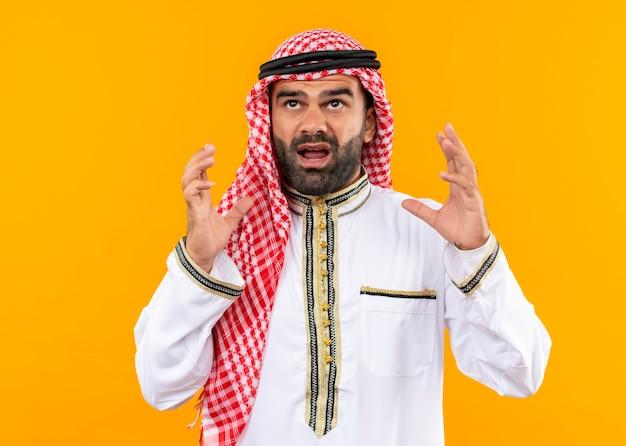 Homme d'affaires arabe frustré dans l'usure traditionnelle en criant avec les mains levées debout sur le mur orange