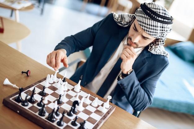 Homme d'affaires arabe jouant aux échecs à table dans une chambre d'hôtel.