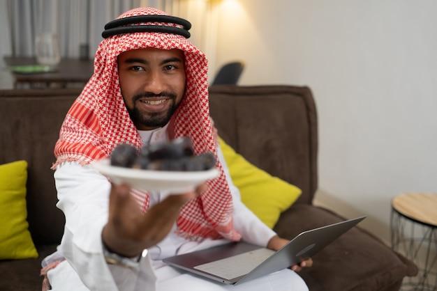 Un homme d'affaires arabe portant un turban portant une assiette de dattes alors qu'il était assis au travail