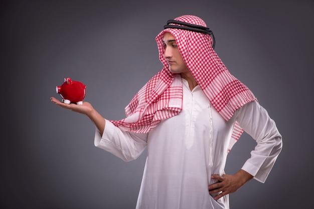 Homme d'affaires arabe avec sa tirelire sur fond gris