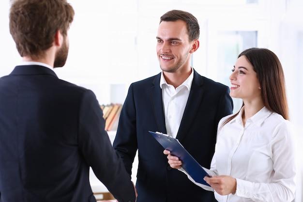 Un homme d'affaires arabe et son traducteur accueillent un partenaire commercial et lui disent bonjour