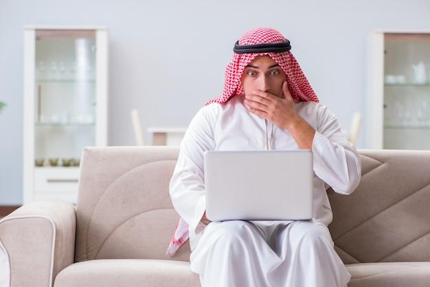 Homme d'affaires arabe travaillant assis sur un canapé
