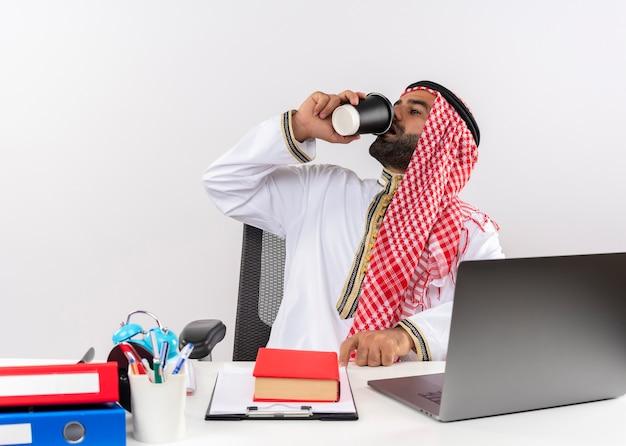 Homme d'affaires arabe en vêtements traditionnels assis à la table avec un ordinateur portable, boire du café au bureau