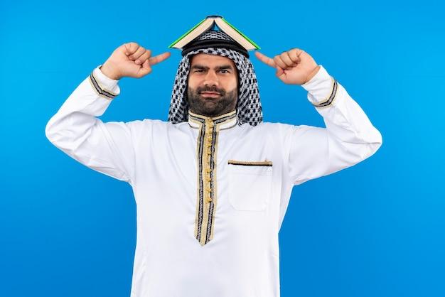 Homme d'affaires arabe en vêtements traditionnels avec livre sur sa tête pointant avec le doigt vers lui souriant debout sur le mur bleu