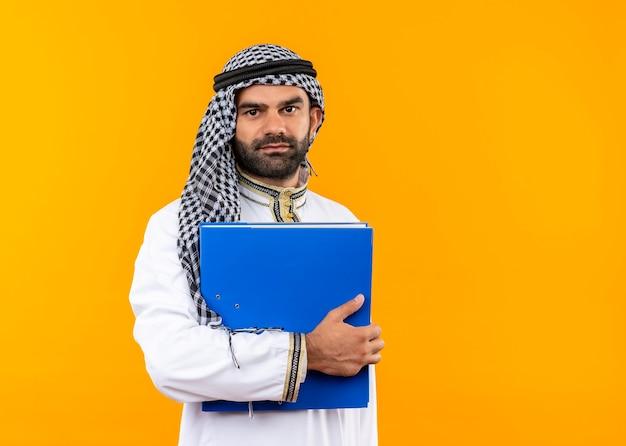 Homme d'affaires arabe en vêtements traditionnels tenant un dossier bleu souriant confiant debout sur un mur orange