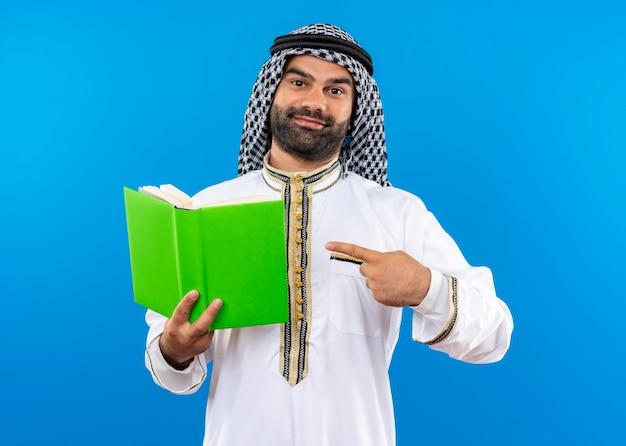 Homme d'affaires arabe en vêtements traditionnels tenant un livre ouvert pointant avec le doigt dessus avec le sourire sur le visage debout sur le mur bleu