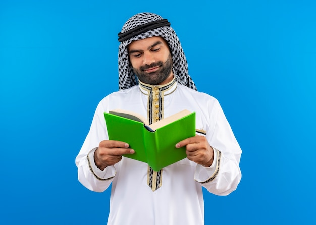 Homme d'affaires arabe en vêtements traditionnels tenant un livre ouvert en le regardant avec le sourire sur le visage debout sur le mur bleu