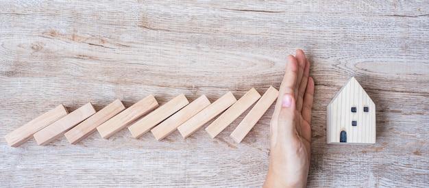 Homme d'affaires arrêter de tomber des blocs de bois et protéger le modèle de maison