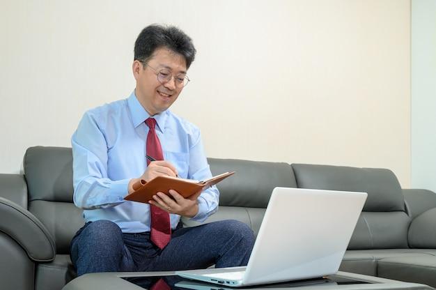 Homme d'affaires asiatique d'âge moyen assis sur le canapé dans le salon, travaillant à la maison. concept de télétravail.