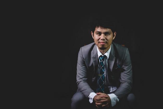 Homme d'affaires asiatique assis sur une chaise et souriant avec un fond noir