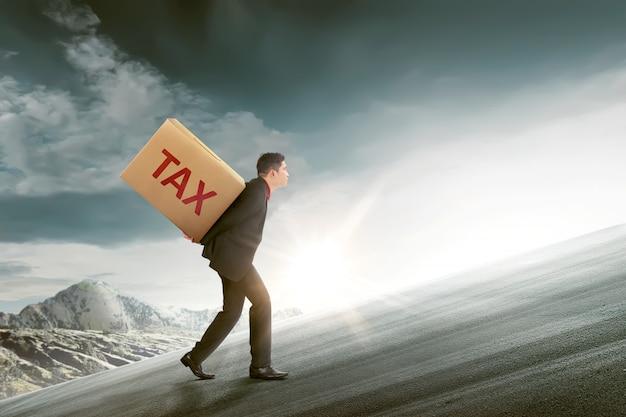 Homme d'affaires asiatique attrayant apporter le carton de la taxe