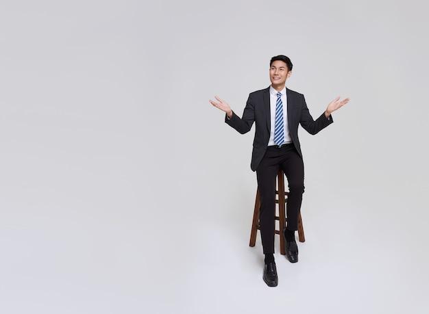 Un homme d'affaires asiatique au visage beau et amical, souriant en costume formel, pointe ses mains vers l'espace de copie sur fond blanc tourné en studio.
