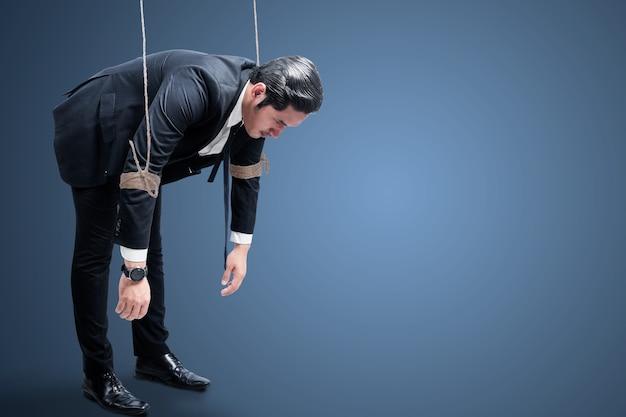 Homme d'affaires asiatique contrôlé avec une corde avec un fond coloré