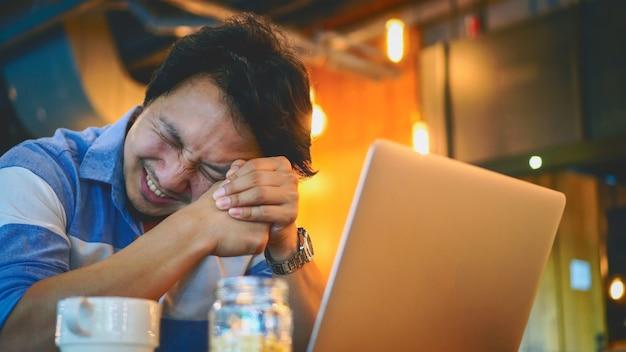 Homme d'affaires asiatique en costume décontracté travaillant avec ordinateur dans une émotion de stress au co-working spa