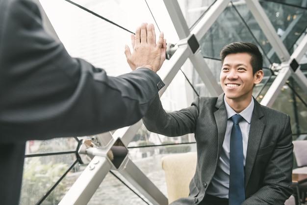 Homme d'affaires asiatique donnant le haut cinq habilitant son partenaire
