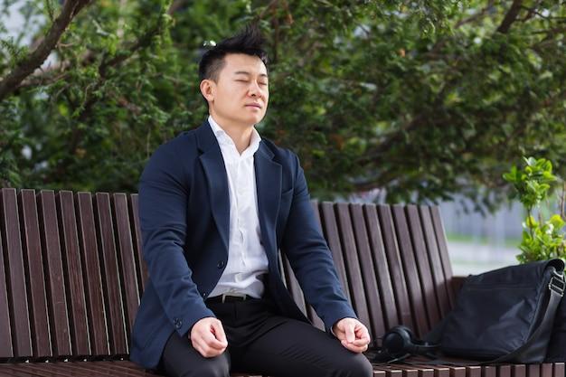Homme d'affaires asiatique effectuant des exercices de respiration essayant de calmer le stress, assis sur un banc pendant une pause déjeuner dans un costume d'affaires