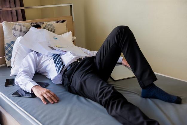 Un homme d'affaires asiatique fatigué dort sur le lit avec une pile de papiers de travail couvrant son visage. travail acharné et pression d'un homme d'affaires faisant la sieste dans la chambre avec des tonnes de documents restants au travail.