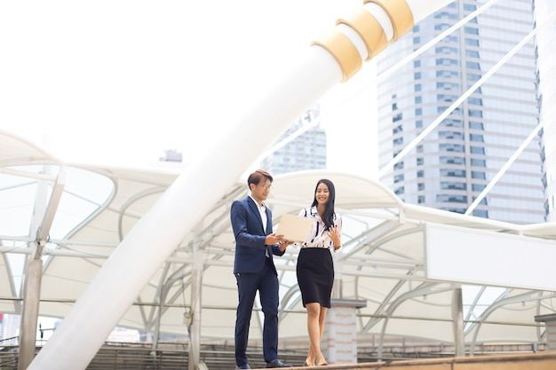 Homme d'affaires asiatique et femme travaillant sur un ordinateur portable à l'extérieur de l'immeuble de bureaux.