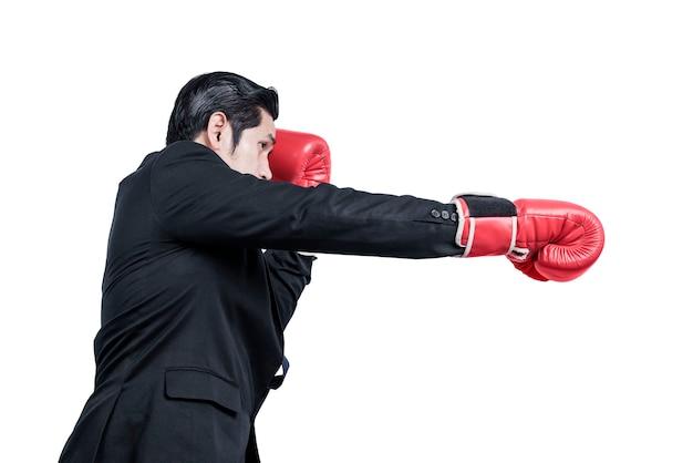 Homme d'affaires asiatique avec des gants de boxe rouges combats isolés sur mur blanc