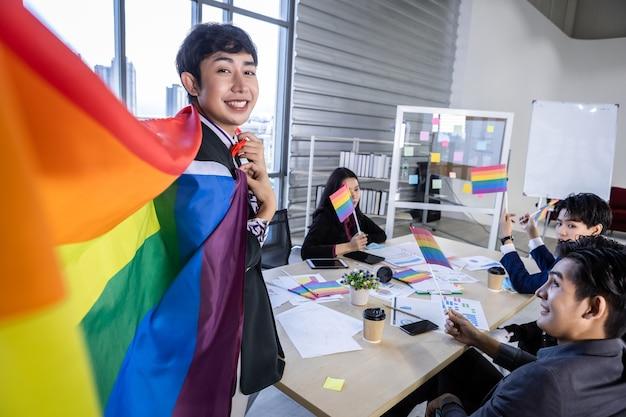 Homme d'affaires asiatique homosexuel avec drapeau lgbt et travailleurs heureux avec succès avec les employés de l'entreprise groupe d'hommes d'affaires asiatiques et soutien dans la salle de réunion au bureau