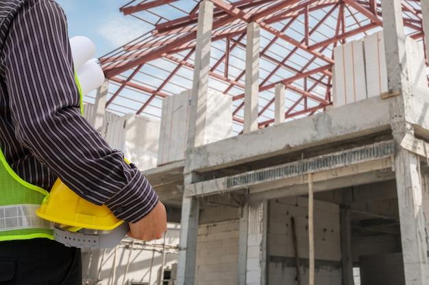 Homme d'affaires asiatique ingénieur en construction travailleur dans un casque de protection et des plans papier sur place au chantier de construction de la maison