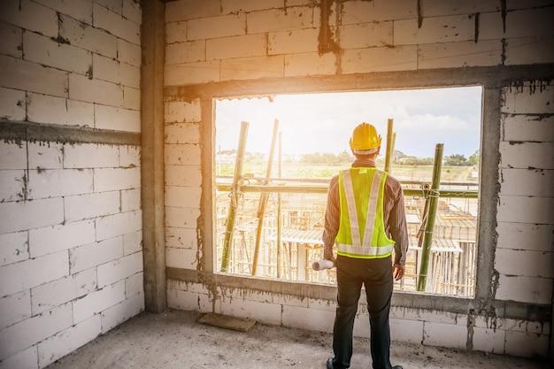 Homme d'affaires asiatique ingénieur en construction travailleur dans un casque de protection et des plans papier sur place au chantier de construction
