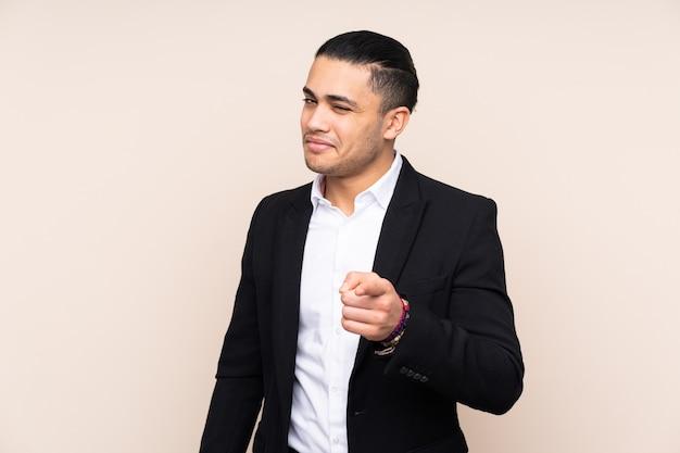 Homme d'affaires asiatique isolé sur fond beige pointe le doigt sur vous