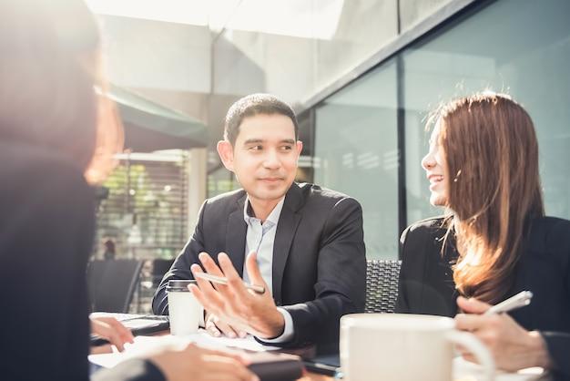 Homme d'affaires asiatique lors d'une réunion d'équipe de café en plein air