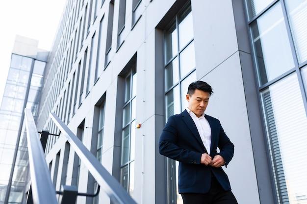 Un homme d'affaires asiatique monte les escaliers du centre de bureaux, l'homme se précipite pour une réunion d'affaires en costume
