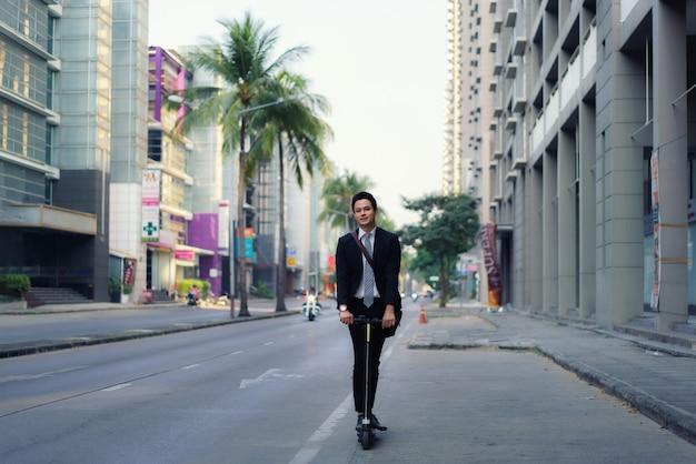 Homme d'affaires asiatique monté sur un scooter électrique dans les rues de la ville pour aller travailler le matin