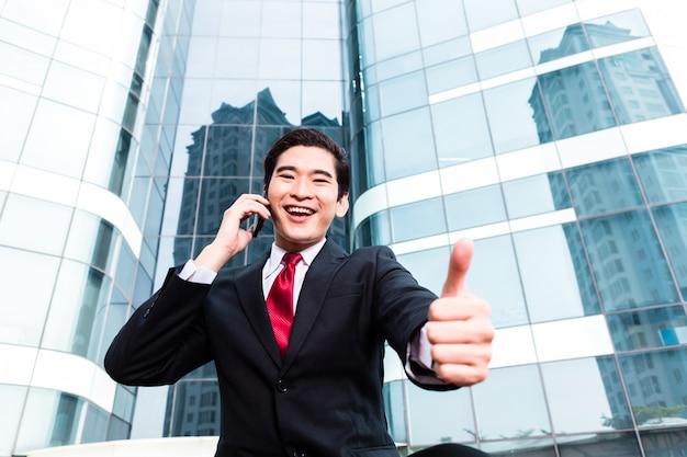Homme d'affaires asiatique parlant à l'extérieur d'un téléphone mobile
