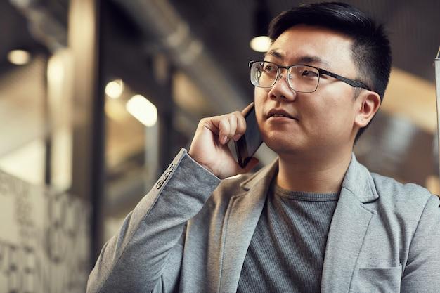 Homme d'affaires asiatique parlant par smartphone