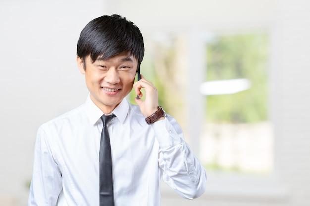 Homme d'affaires asiatique parlant sur un téléphone mobile