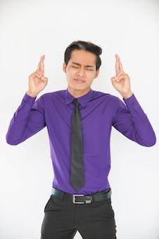 Homme d'affaires asiatique en phase de cuisson en train de garder les doigts croisés