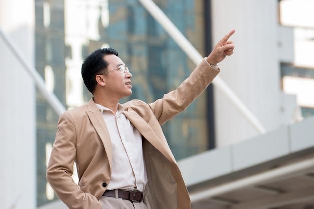 Homme d'affaires asiatique pointant sur quelque chose et en regardant