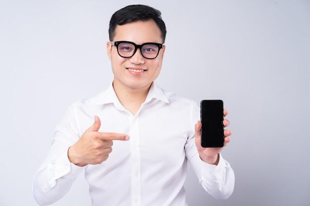 Homme d'affaires asiatique pointant vers l'écran du smartphone