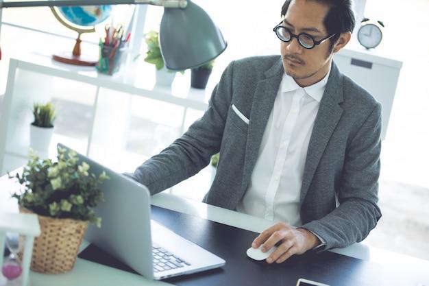 Homme d'affaires asiatique portant des lunettes au bureau.