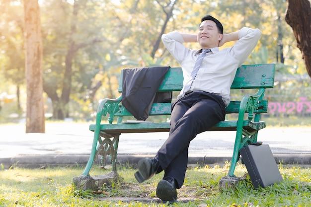 Homme d'affaires asiatique portrait assis sur une chaise en bois vert détente dans le parc