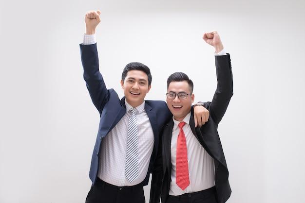 Un homme d'affaires asiatique prospère se sent heureux ou gagne avec un arrière-plan, un démarrage, un travail intelligent, des personnes à succès, un concept de partenaire et de travail d'équipe