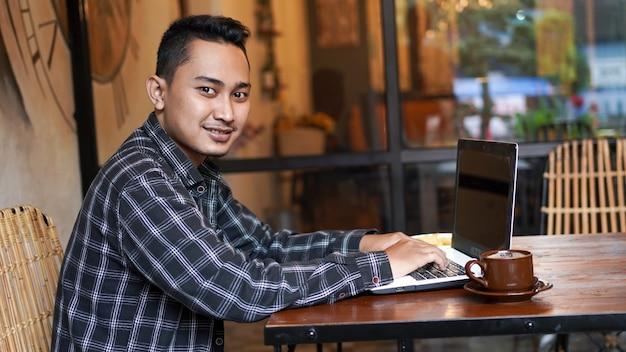 Homme d'affaires asiatique tapant sur ordinateur portable au café