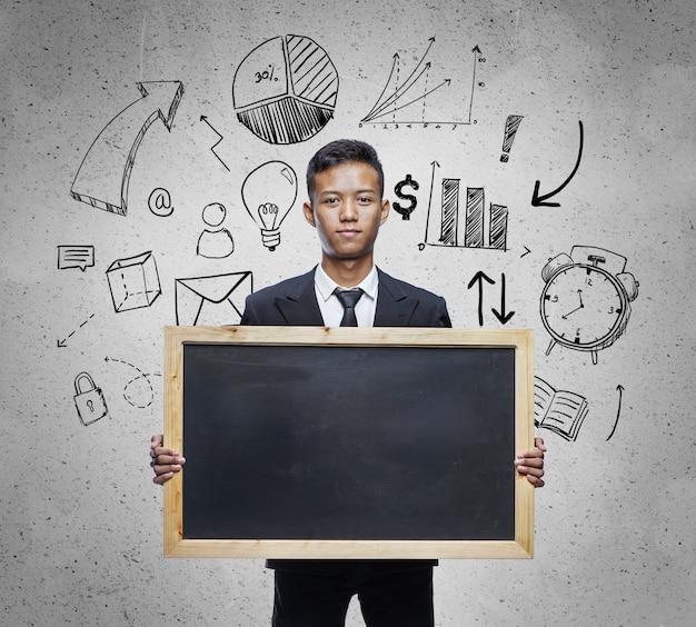 Homme d'affaires asiatique tenant grand tableau. fond de business sketch concept. place au texte