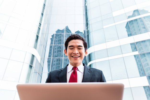 Homme d'affaires asiatique travaillant sur un ordinateur portable en face du bâtiment de la tour