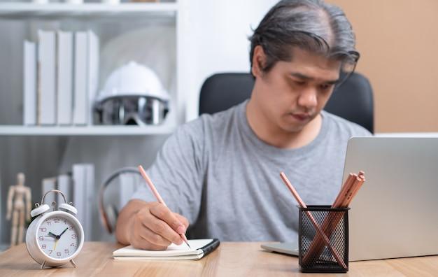 Homme d'affaires asiatique travaille à la maison la nuit pour résoudre les problèmes commerciaux