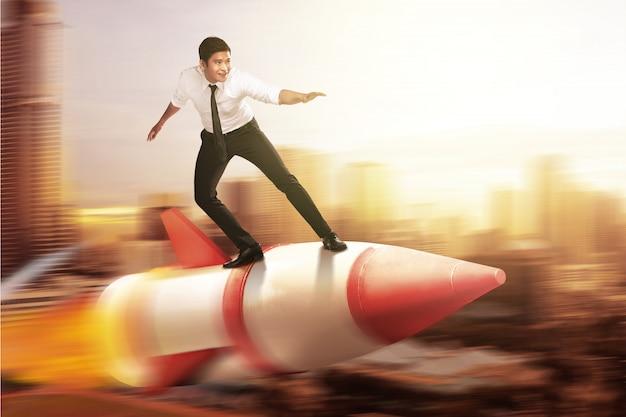 Homme d'affaires asiatique volant sur une fusée